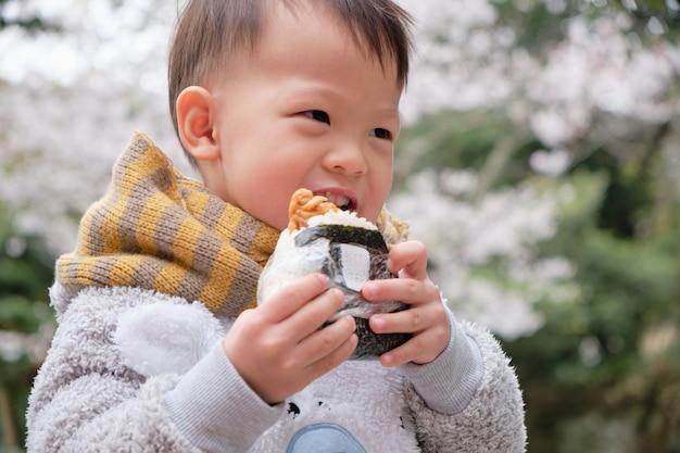 Netter kleiner asiatischer kleinkindjunge, der onigiri, japanisches lebensmittel, japanischer reisball, reisdreieck mit meerespflanze im blütenfrühlingsgarten bei der besichtigung von kirschblüte beißt u. isst