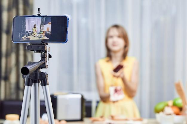 Netter kleiner blogger mit lebensmittelaufzeichnungsvideo auf einer küche