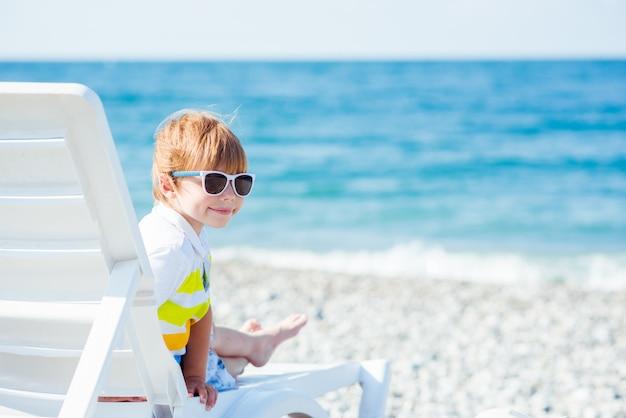Netter kleiner blonder junge in der sonnenbrille sitzt auf sunbed auf der ozeanküste