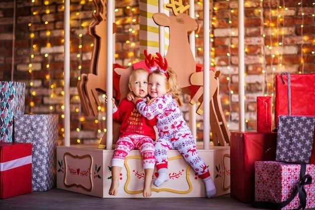 Netter kleiner blonder junge und mädchen, die auf dem weihnachtskarussell sitzen, umgeben von weihnachtsgeschenken. foto in hoher qualität