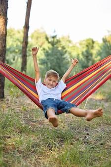 Netter kleiner blonder kaukasischer junge, der spaß mit bunter hängematte im hinterhof oder spielplatz im freien hat. sommer aktive freizeit für kinder. kind auf hängematte. aktivitäten und spaß für kinder im freien