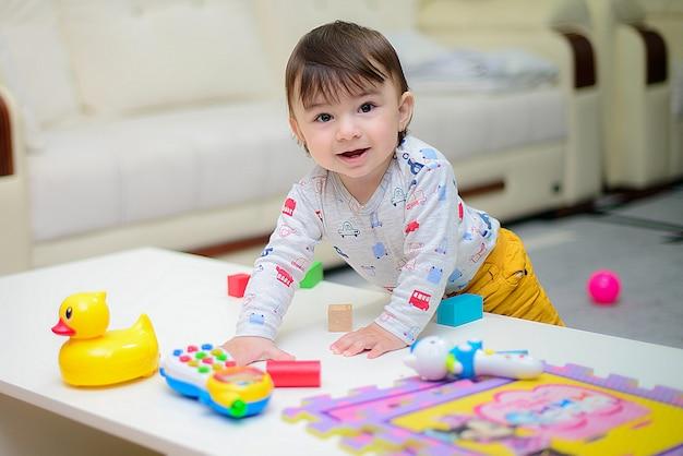 Netter kleiner genießender junge beim spielen mit spielwaren oder blöcken an seinem raum