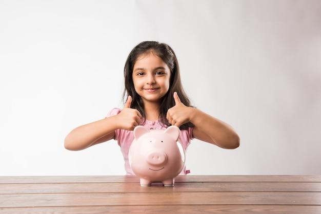 Netter kleiner inder oder asiate mit sparschwein, münzen setzen oder nachdenken oder daumen nach oben zeigen. planung für die zukunft