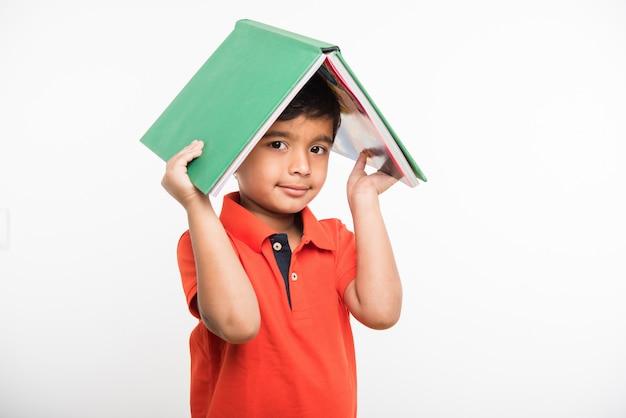 Netter kleiner indischer asiatischer junge mit ausgestreckten händen, der ein buch, eine lupe oder eine siegestrophäe hält und isoliert auf weißem hintergrund steht