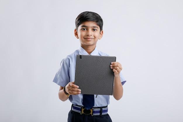 Netter kleiner indischer / asiatischer schuljunge, der notizbuch zeigt