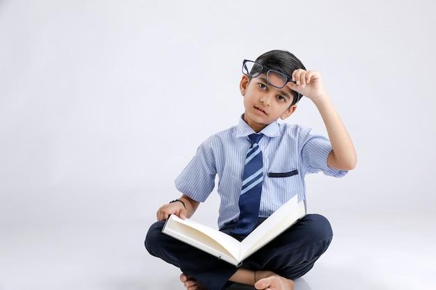 Netter kleiner indischer / asiatischer schuljunge mit brillen-lesebuch
