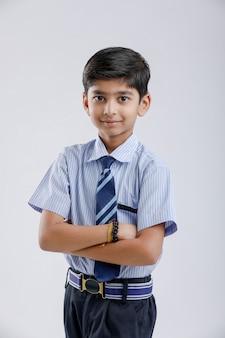 Netter kleiner indischer indischer / asiatischer schuljunge, der uniform trägt