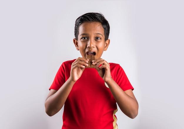 Netter kleiner indischer junge, der schokolade isst, lokalisiert auf weißem hintergrund,