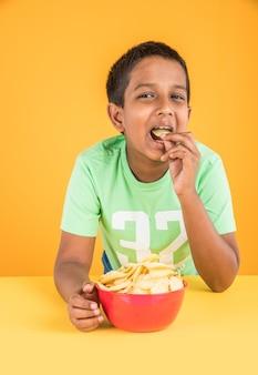 Netter kleiner indischer oder asiatischer junge, der chips oder kartoffelwaffeln in großer roter schüssel isst, auf gelbem hintergrund