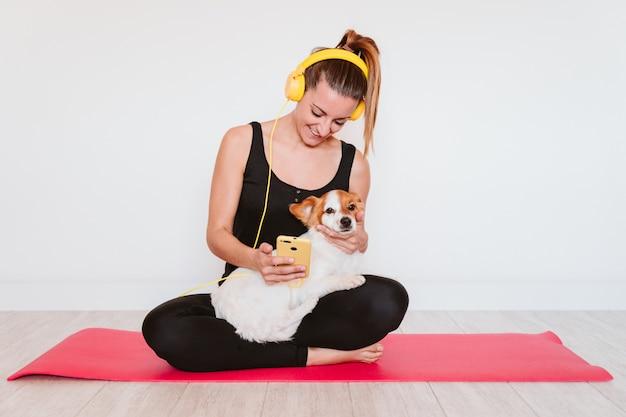 Netter kleiner jack russell hund, der yoga auf einer matte zu hause mit ihrem besitzer tut. junge frau, die musik auf gelbem handy und headset hört. gesunder lebensstil drinnen