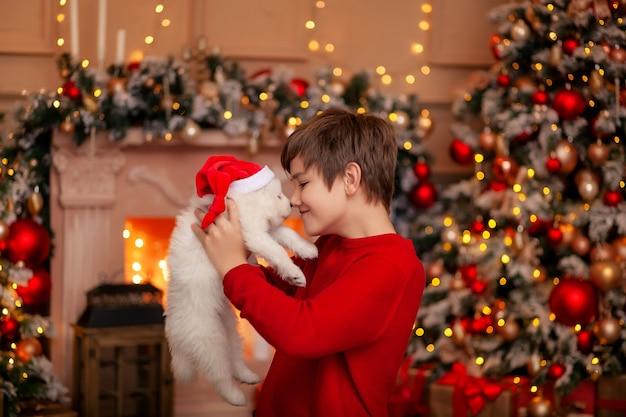 Netter kleiner junge am weihnachtsbaum mit einem hund, der auf frohe weihnachten wartet