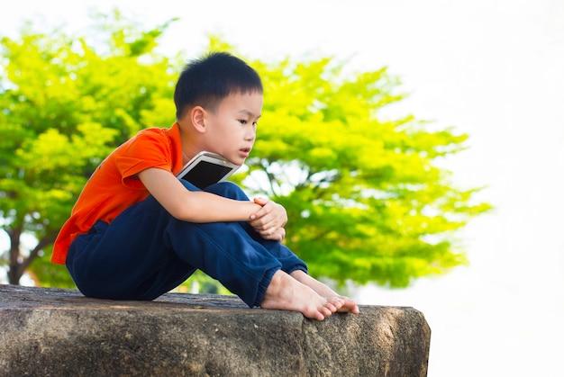 Netter kleiner junge benutzen eine tablette beim sitzen im park