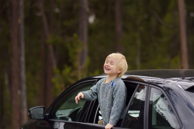 Netter kleiner junge bereit zu einem roadtrip oder zu einer reise. familienauto mit kindern.