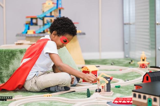 Netter kleiner junge der afrikanischen ethnischen zugehörigkeit, der weiße freizeitkleidung und roten mantel des übermenschen trägt, der im kindergarten spielt