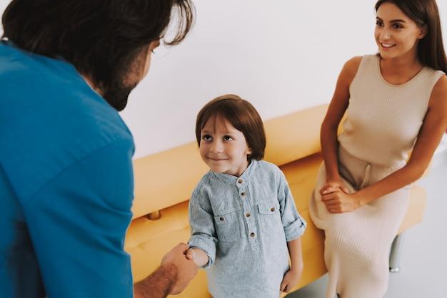 Netter kleiner junge, der an doktor und am händeschütteln lächelt
