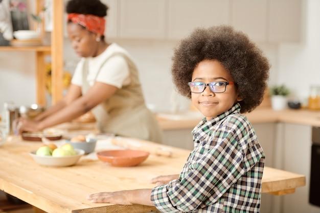 Netter kleiner junge, der an einem hölzernen küchentisch gegen seine mutter steht