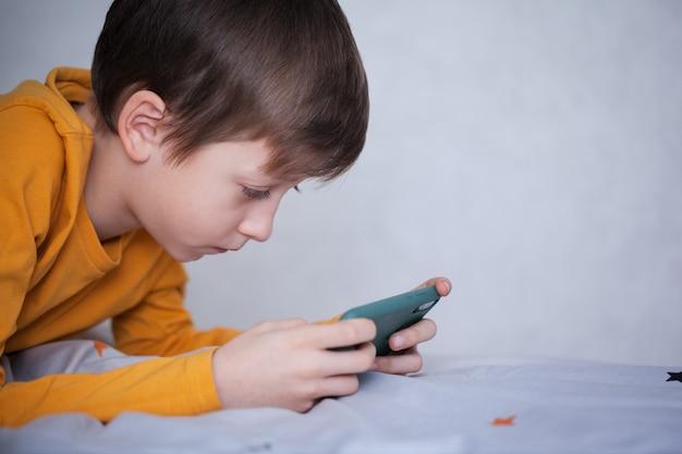 Netter kleiner junge, der auf dem bett lag, konzentrierte sich auf smartphone