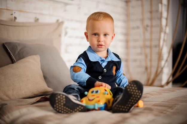 Netter kleiner junge, der auf dem bett mit einem spielzeug sitzt