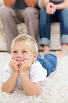 Netter kleiner junge, der auf dem boden liegt und fernsehen mit seinen eltern aufpasst