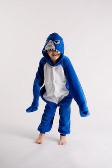 Netter kleiner junge, der auf einem weißen hintergrund in den pyjamas, blauhaikostüm aufwirft