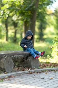 Netter kleiner junge, der auf einer holzbank stillsteht
