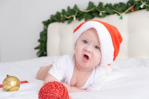 Netter kleiner junge, der auf weißem bettzeug zu hause mit weihnachtsmütze und weihnachtsdekorationen liegt.