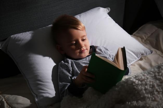 Netter kleiner junge, der buch im bett zu hause liest
