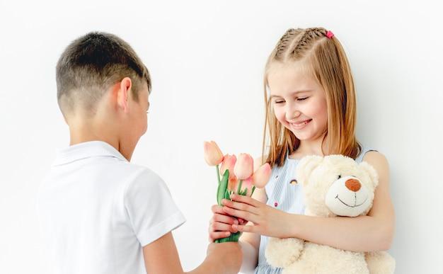 Netter kleiner junge, der dem lächelnden mädchenkind geschenk gibt