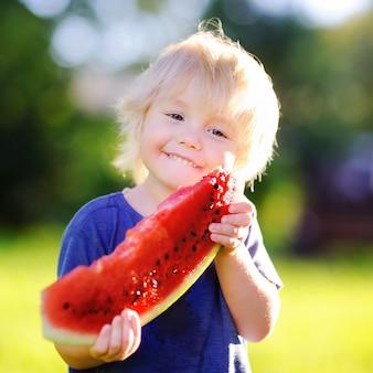 Netter kleiner junge, der draußen frische wassermelone isst
