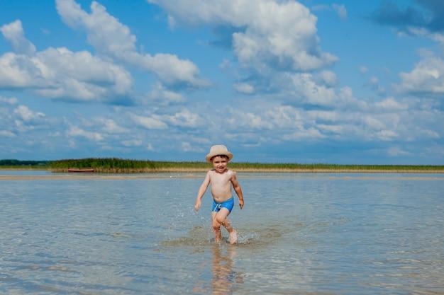 Netter kleiner junge, der durch das wasser am strand läuft