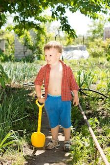Netter kleiner junge, der eine kleine plastikschaufel hält, während er an einem sonnigen sommertag im garten arbeitet