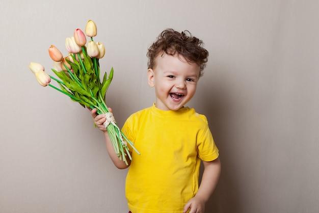 Netter kleiner junge, der einen blumenstrauß der blumen anhält. tulpen muttertag.