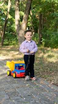 Netter kleiner junge, der einen bunten spielzeuglastwagen hinter sich auf einer gepflasterten gasse im wald zieht