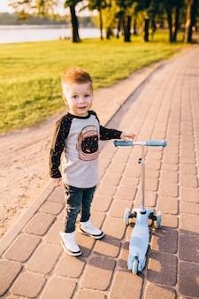 Netter kleiner junge, der einen tretroller reitet. gesunde outdoor-aktivität