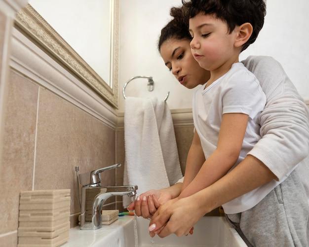 Netter kleiner junge, der hände mit seiner mutter wäscht