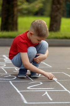 Netter kleiner junge, der himmel mit kreide auf dem spielplatz zeichnet. lustiges aktivitätsspiel für kinder auf dem spielplatz draußen.