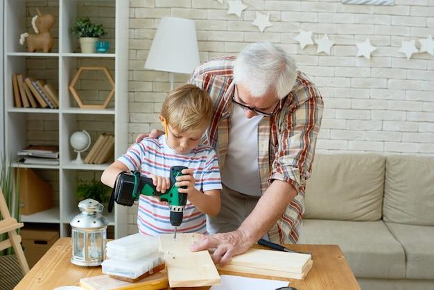 Netter kleiner junge, der holz mit hilfe von opa bohrt