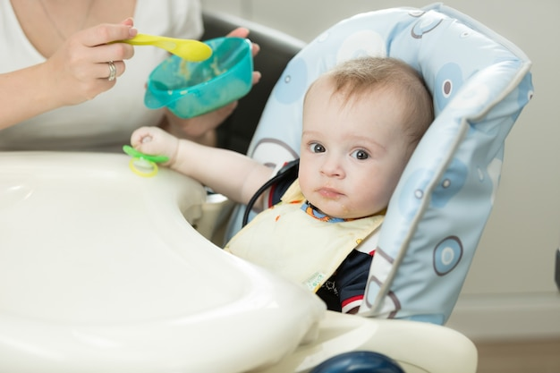 Netter kleiner junge, der im hochstuhl an der küche sitzt