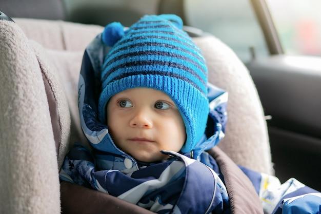 Netter kleiner junge, der im kindersitz in einem auto sitzt und winteroverall und hutbild mit...