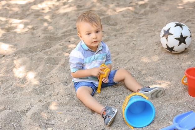 Netter kleiner junge, der im sandkasten draußen spielt