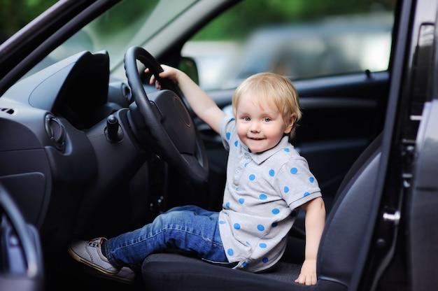 Netter kleiner junge, der im vaterauto spielt