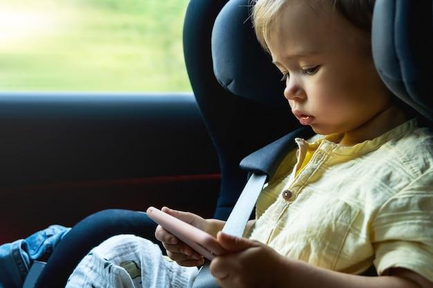 Netter kleiner junge, der in einem babysitz in einem auto sitzt