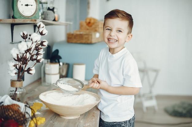Netter kleiner junge, der in einer küche sitzt