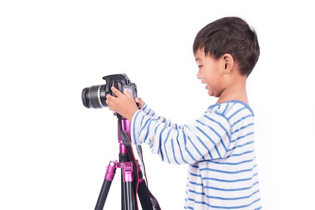 Netter kleiner junge, der kamera nimmt