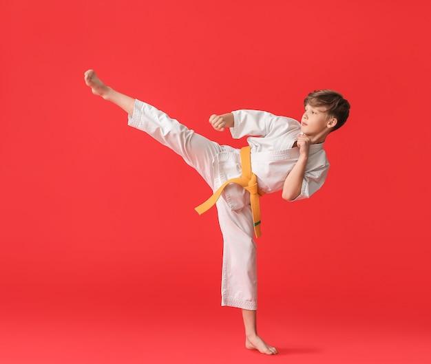 Netter kleiner junge, der karate übt