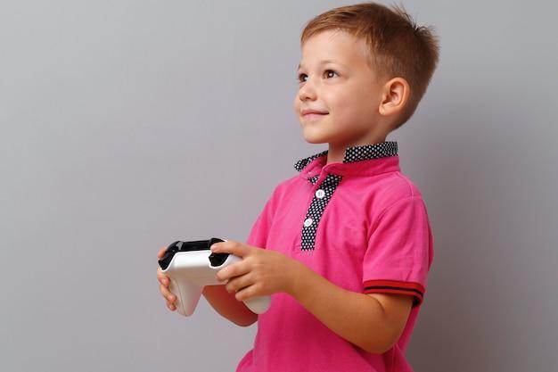 Netter kleiner junge, der konsole über einem grauen hintergrund spielt