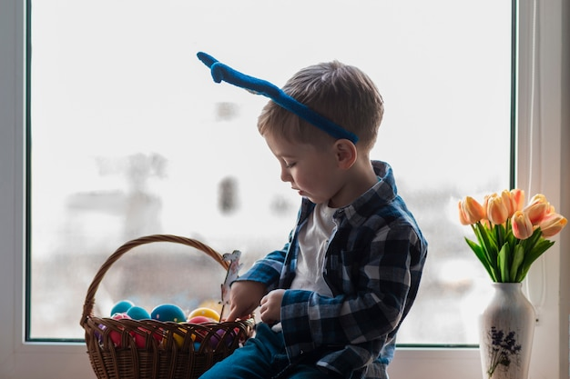 Netter kleiner junge, der korb mit eiern prüft