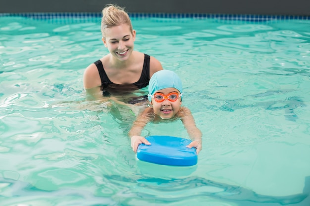 Netter kleiner junge, der lernt, mit trainer zu schwimmen