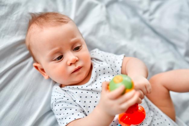 Netter kleiner junge, der mit einem bunten spielzeug spielt, während er zu hause auf dem bett liegt.