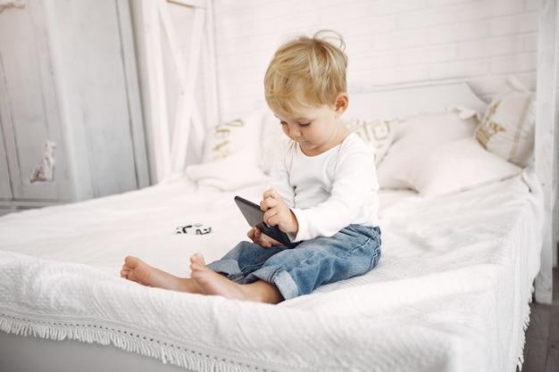 Netter kleiner junge, der mit einem laptop auf einem bett spielt